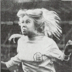 woman with long blonde hair jumping for a football