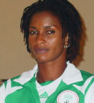 A woman of colour smiling enigmatically and wearing a green and white tracksuit