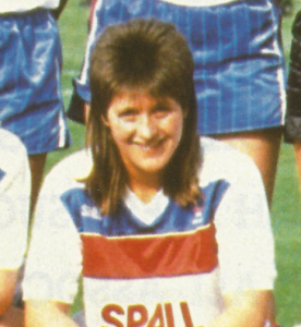 Smiling woman with brown shoulder-length hair in a white t-shirt with blue and red stripes