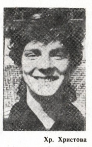 A black and white newspaper photograph of a smiling woman's face. She has curly hair and prominent cheek bones