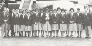 A group of about 20 women stand in front of an airplane wearing dowdy skirt suits