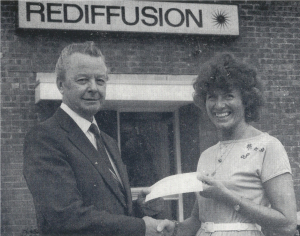June Jaycocks smiling outside Rediffusion's building, shaking hands with and accepting a cheque from the company's manager
