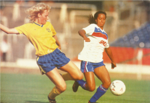 Two women footballers challenge for the ball in the bottom right of the picture