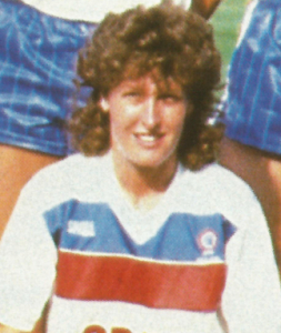 A smiling woman with curly brown hair in a red, white and blue T-shirt