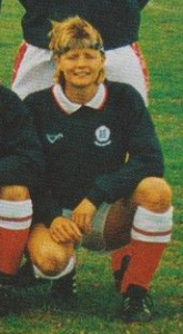 A crouching smiling blond haired woman in a football kit with red socks, white shorts, a blue sweatshirt and a blue headband